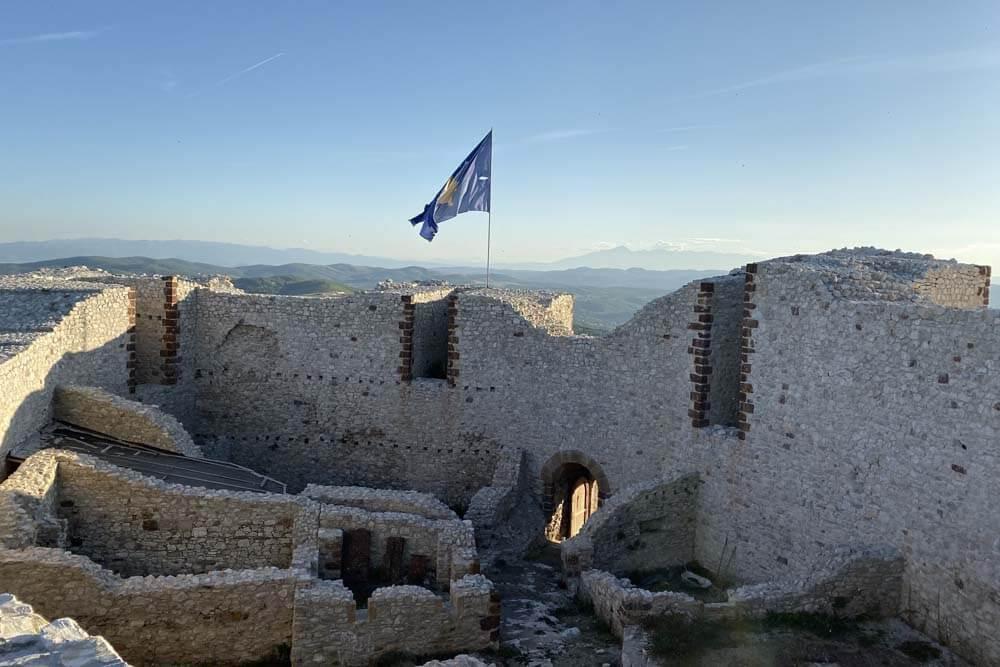 Ruine und Berge mit Kosovo Flagge Mietwagenrundreise Kosovo